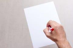 Equipaggia la mano con un foglio di carta dello spazio in bianco e della penna a sfera bianco su un fondo grigio, primo piano di  Immagine Stock