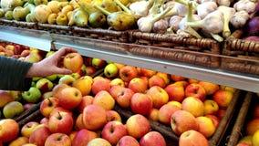 A equipaggia la mano seleziona le mele in una finestra del negozio, frutta e le verdure si trovano merci nel carrello stock footage