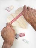 Equipaggia le mani che avvolgono un contenitore di regalo a forma di cuore con un nastro Fotografia Stock Libera da Diritti