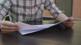 Equipaggia le mani che il selezionare riveste con i disegni nell'ufficio di affari Nessun fronte archivi video