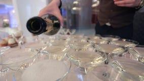 Equipaggia le mani versano il champagne nei vetri di martini dello speciale Nessun fronte stock footage
