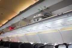 Equipaje de cabina de arriba en el aeroplano Imagenes de archivo