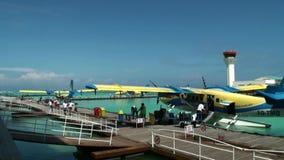 Equipaje de la transferencia directa de la gente en el hidroavión amarillo que coloca el embarcadero cercano en el océano almacen de video