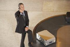Equipaje de Using Cellphone By del hombre de negocios en el carrusel en aeropuerto fotografía de archivo