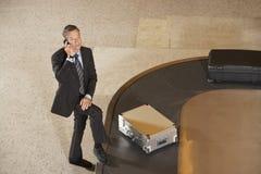 Equipaje de Using Cellphone By del hombre de negocios en el carrusel en aeropuerto imagen de archivo