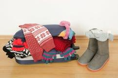 Equipaje del invierno La maleta de marchita por completo la ropa Foto de archivo libre de regalías