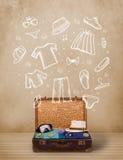 Equipaje del viajero con ropa e iconos dibujados mano Imagen de archivo