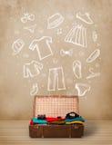 Equipaje del viajero con ropa e iconos dibujados mano Foto de archivo libre de regalías