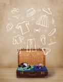 Equipaje del viajero con ropa e iconos dibujados mano Foto de archivo