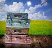 Equipaje del vintage en la tabla de madera con el fondo agradable del paisaje Fotos de archivo libres de regalías