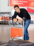 Equipaje que espera del hombre para de la banda transportadora en el aeropuerto Imagen de archivo