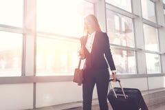 Equipaje que lleva femenino bastante sonriente del asistente de vuelo que va al aeroplano en el aeropuerto fotos de archivo libres de regalías