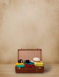 Equipaje turístico retro con ropa y copyspace coloridos Imagen de archivo