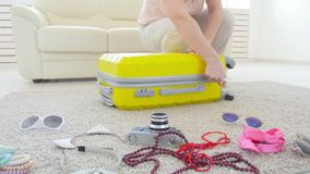 Equipaje y concepto del viaje La mujer joven pone cosas en una maleta para un viaje de las vacaciones almacen de metraje de vídeo