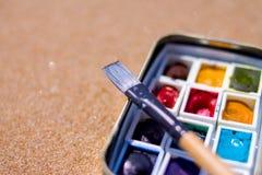 Equipamento artístico: escovas de pintura, pinturas das aquarelas no fundo da areia no dia de verão ensolarado - criação, desenho foto de stock