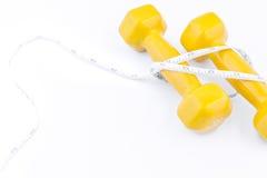 Equipamento da aptidão Peso amarelo com a fita de medição no branco Foto de Stock