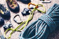 Equipamento da escalada e do alpinismo em um tapete Sapatas, carabina, corda, galope, ascendente Conceito do esporte exterior e e imagem de stock royalty free