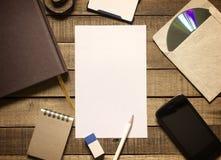 Equipamento de escritório do papel para cartas e dos artigos de papelaria no fundo de madeira Imagens de Stock
