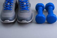 Equipamento de esporte - sapatilhas e pesos no fundo cinzento Fotografia de Stock