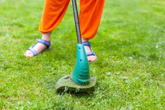 Equipamento de jardim Jovem mulher que sega a grama com um ajustador Fotos de Stock Royalty Free