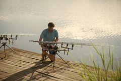 Equipamento de pesca do reparo do homem no cais de madeira fotos de stock royalty free