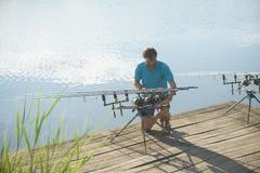 Equipamento de pesca do reparo do homem no cais de madeira imagem de stock
