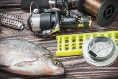 Equipamento de pesca e brema pescada em uma tabela de madeira fotos de stock royalty free