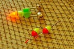 Equipamento de pesca - giro, ganchos e atrações da pesca no fundo de madeira claro Imagem de Stock Royalty Free