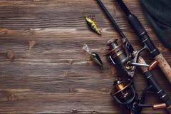 Equipamento de pesca - giro, ganchos e atrações da pesca no CCB de madeira foto de stock