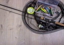 Equipamento de pesca - giro, ganchos e atrações da pesca no fundo de madeira fotos de stock
