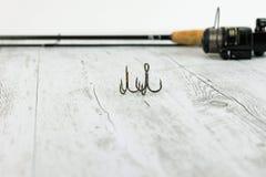 Equipamento de pesca - giro, ganchos e atrações da pesca no fundo de madeira branco Vista superior Imagem de Stock