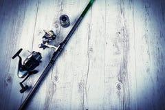 Equipamento de pesca - giro, ganchos e atrações da pesca no fundo de madeira branco Vista superior Imagens de Stock