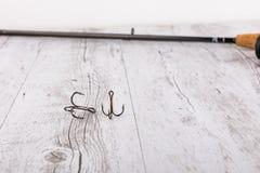 Equipamento de pesca - giro, ganchos e atrações da pesca no fundo de madeira branco Vista superior Fotografia de Stock Royalty Free