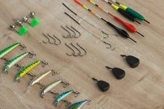 Equipamento de pesca moderno - pescando o flutuador, as atrações, os pesos e os sinos no fundo de madeira bonito fotografia de stock royalty free