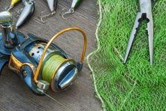 Equipamento de pesca - o giro, os ganchos e as atrações da pesca escurecem sobre o fundo de madeira imagens de stock royalty free