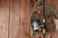 Equipamento de pesca - vara de pesca que pesca o flutuador e as atrações no fundo de madeira azul bonito, espaço da cópia imagem de stock royalty free