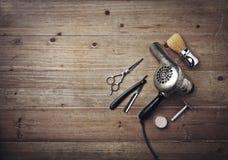 Equipamento do barbeiro do vintage no fundo de madeira com lugar para o texto