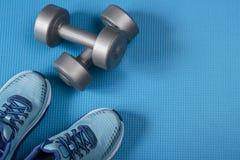 Equipamento e sapatas de esporte no fundo azul Vista superior fotografia de stock