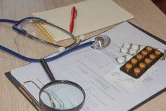 Equipamento médico com comprimidos e no fundo de madeira da mesa do doutor, conceito médico horizontal foto de stock