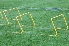 Equipamento para o treinamento do futebol Barreiras de salto e anéis de formação no gramado Ostenta o fundo Fotos de Stock