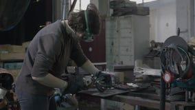 Equipamento vestindo da proteção do soldador ou do ferreiro da mulher profissional das faíscas que moem o aço e o ferro lisos em  vídeos de arquivo