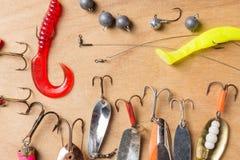 Equipamentos de pesca diferentes e sem-fins plásticos no fundo da placa de madeira Foto de Stock