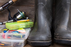 Equipamentos de pesca e botas de borracha na placa da madeira Imagens de Stock Royalty Free
