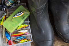 Equipamentos de pesca e botas de borracha na placa da madeira Foto de Stock Royalty Free