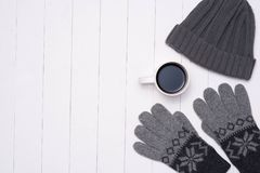Equipamentos ocasionais do inverno do ` s dos homens com o copo de café no fundo de madeira Foto de Stock Royalty Free