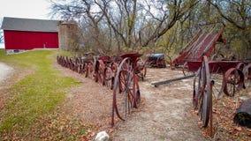 Equipamiento agrícola antiguo y granero rojo imagen de archivo libre de regalías