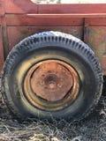 Equipamiento agrícola rojo viejo con el neumático oxidado fotografía de archivo