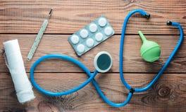 Equipamiento médico del terapeuta en una tabla de madera: estetoscopio, enema, termómetro, tabletas, vendaje Visión superior Imágenes de archivo libres de regalías