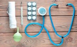 Equipamiento médico del terapeuta en una tabla de madera: estetoscopio, enema, termómetro, tabletas, vendaje Visión superior Foto de archivo