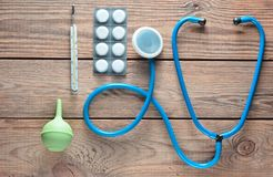 Equipamiento médico del terapeuta en una tabla de madera: estetoscopio, enema, termómetro, tabletas, vendaje Visión superior Fotos de archivo